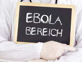 Doctor shows information: Ebola area in german language — Stock Photo