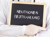 Doctor shows information: neutron radiation in german — Stock Photo