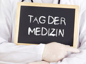 Doctor shows information: Doctors Day in german language — Stock Photo
