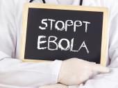 Doctor shows information: stop Ebola in german language — Stock fotografie