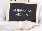 Doctor shows information on blackboard: alternative medicine — Stock Photo