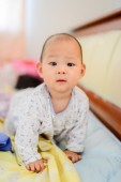 Happy Asian baby on bed. — ストック写真