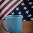 Blue coffee cup on wooden table with USA flag background. — Stock Photo #56203931