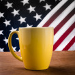 Yellow coffee cup on wooden table with USA flag background. — Stock Photo #56204043