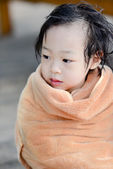 Wet Asian baby girl in brown towe. — Stock Photo
