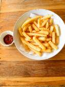 French fries closeup over wood — Stock Photo