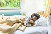 Asian girl sleeping on bed covered with blanket. — Stock Photo
