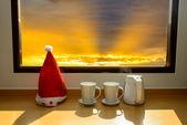Santa hat with coffee mug near window facing to sun rise with na — Stock Photo