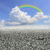 Drought land against a blue sky with clouds and rainbow — Stock Photo