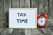 Tax time message note on white board with red retro clock on woo — Stock Photo