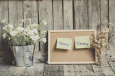 Vintage style effect Happy Tuesday message on corkboard with flo — Stock Photo