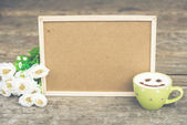 Cockboard with coffee and flower on wooden table in vintage tone — Стоковое фото