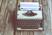 Vintage typewriteron the wood desk in old tone — Stock Photo
