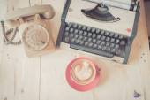 Red latte coffee cup with vintage telephone and typewriter on wo — Стоковое фото