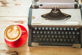 Typewriter and red coffee cup on wooden background. — Стоковое фото