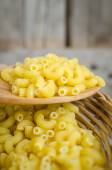 Italian Macaroni Pasta on basketwork with wooden texture backgro — Stock Photo