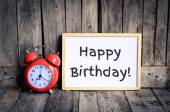 Happy birthday messae on white board and red retro clock by wooden background — Stock Photo