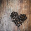 Heart shape made from coffee beans on wooden surface. — Stock Photo #70728575
