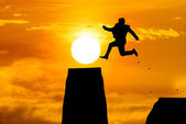 Silhouette Man Jumping in sun rise. — Stock Photo