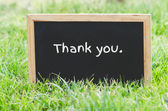 Thank you message on blackboard on green grass. — Stock Photo