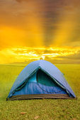 Sun rise over camping tent inside grassy field — Stock Photo
