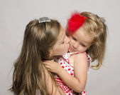 Young girl holding in her arms and kissing and having fun with her small sister. Kids playing and laugh — Stock Photo