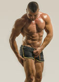 Strong bodybuilder man with perfect abs, shoulders,biceps, triceps and chest, personal fitness trainer — Stock Photo