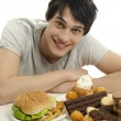Young man holding in front lots of cookies and a big hamburger. Choosing between chocolate, cupcakes, biscuits and a burger. Trying to get fat eating fast food and lots of sugar — Stock Photo #54029921