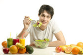 Man having a table full of organic food,juices and smoothie. Cheerful young man eating healthy salad,fruits and drinking organic smoothie. Isolated on white — Stock Photo