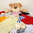 Bear toy on a bed with different colorful new born clothes.Colorful wardrobe of newborn,kids, babies full of all clothes, shoes,accessories and toys — Stock Photo #62825797