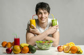Man having a table full of organic food,juices and smoothie. Cheerful young man eating healthy salad and fruits. Isolated on white — Stock Photo