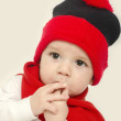 Innocent baby wearing a red hat and a muffler and looking adorable. Small kid dressed for winter. Newborn eating his fingers — Stock Photo #64464475