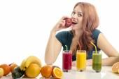 Mulher feliz tendo uma mesa cheia de smoothie, sucos e alimentos orgânicos. Jovem alegre comendo frutas e salada saudável. Isolado no branco. Garota comendo uma maçã vermelha fresca. — Fotografia Stock