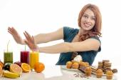 Woman choosing between fruits, smoothie and organic healthy food against sweets, sugar, lots of candies, unhealthy food. Treating your sweets addiction with fruits and vegetables — Stock Photo