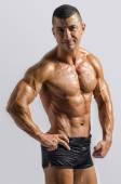 Close-up no fisiculturista forte de Abs perfeito com tanquinho. Homem forte fisiculturista com abs perfeito, ombros, bíceps, tríceps e peito, instrutor de fitness pessoal flexionando seus músculos — Fotografia Stock