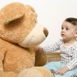 Beautiful innocent newborn speaking with his best friend, teddy bear. Adorable baby playing, having fun with his bear toy. Little sweet kid talking and listening his toy — Stock Photo #70737599