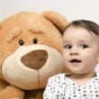 Beautiful innocent newborn speaking with his best friend, teddy bear. Adorable baby playing, having fun with his bear toy. Little sweet kid talking and listening his toy — Stock Photo #70737607