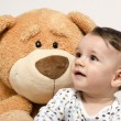 Beautiful innocent newborn speaking with his best friend, teddy bear. Adorable baby playing, having fun with his bear toy. Little sweet kid talking and listening his toy — Stock Photo #70737609