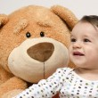Beautiful innocent newborn speaking with his best friend, teddy bear. Adorable baby playing, having fun with his bear toy. Little sweet kid talking and listening his toy — Stock Photo #70737611