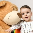 Beautiful innocent newborn speaking with his best friend, teddy bear. Adorable baby playing, having fun with his bear toy. Little sweet kid talking and listening his toy — Stock Photo #70737615