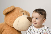 Beautiful innocent newborn speaking with his best friend, teddy bear. Adorable baby playing, having fun with his bear toy. Little sweet kid talking and listening his toy — Stock Photo