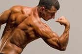 Culturista mostrando su espalda, hombros, tríceps y bíceps músculos, trainer personal fitness — Foto de Stock