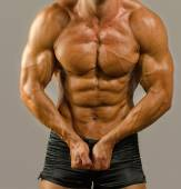 Strong bodybuilder with six pack.Strong bodybuilder man with perfect abs, shoulders,biceps, triceps and chest, personal fitness trainer flexing his muscles — Stock Photo