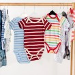 Dressing closet with clothes arranged on hangers.Colorful onesie of newborn,kids, toddlers, babies on a rack.Many colorful t-shirts, shirts,blouses, onesie hanging — Stock Photo #80465736