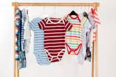 Dressing closet with clothes arranged on hangers.Colorful onesie of newborn,kids, toddlers, babies on a rack.Many colorful t-shirts, shirts,blouses, onesie hanging — Stock Photo