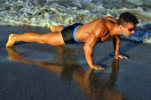 Strong bodybuilder with six pack.Fitness trainer with perfect abs, shoulders,biceps, triceps,chest, flexing his muscles on the beach, training in vacation, doing push ups in the sand — Stock Photo
