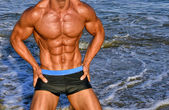 Strong bodybuilder with six pack.Fitness trainer with perfect abs, shoulders,biceps, triceps,chest, flexing his muscles on the beach with sea waves on the background, training in vacation — Stock Photo