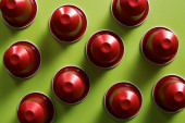 Red coffee capsules on green background — Stock Photo