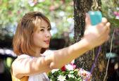 Menina asiática tomando flor de preensão de foto selfie no jardim — Fotografia Stock