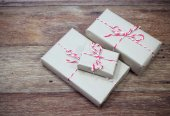 Brown paper parcel tied with red and white string on wood table — Stock Photo